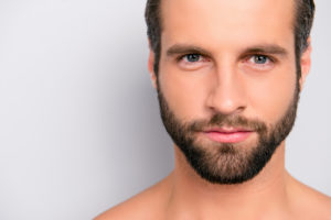 Close up cropped portrait with copy space of virile, harsh, manly, attractive, naked, unshaven, handsome, stunning man with ideal, perfect face skin, looking at camera, isolated on gray background