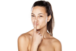 young girl without make up, and pursed lips, kissing her finger